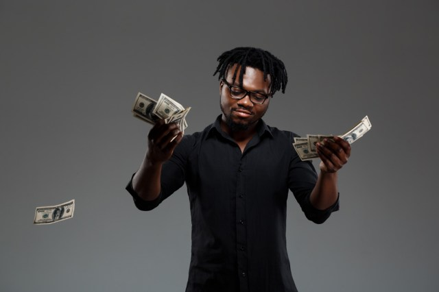 young-successful-african-businessman-throwing-money-darsk