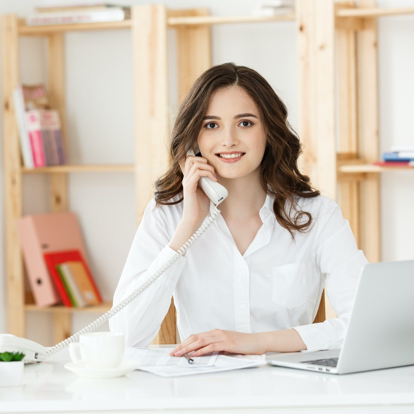 Young woman talking on phone in modern office