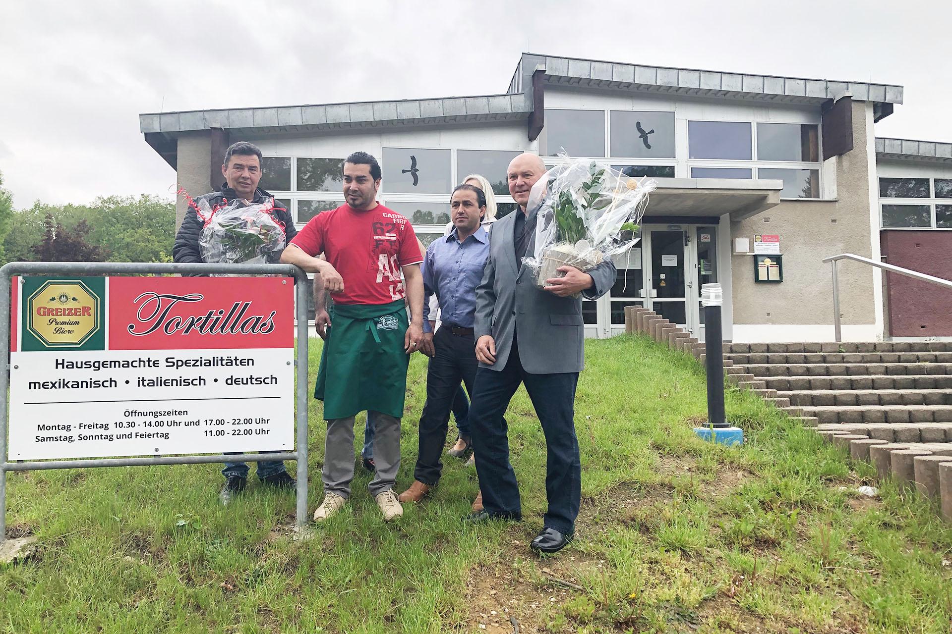 Frank Böttger (r.) und Jan Popp überreichen dem neuen Inhaber der Bad-Gaststätte, Herrn Shinwari, einen Blumengruß