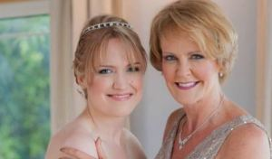 Mother and daughter pose, smiling and radiant, on Lauren's wedding day