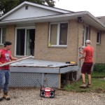 two young men dismantle a grey deck from the back of our tan brick house