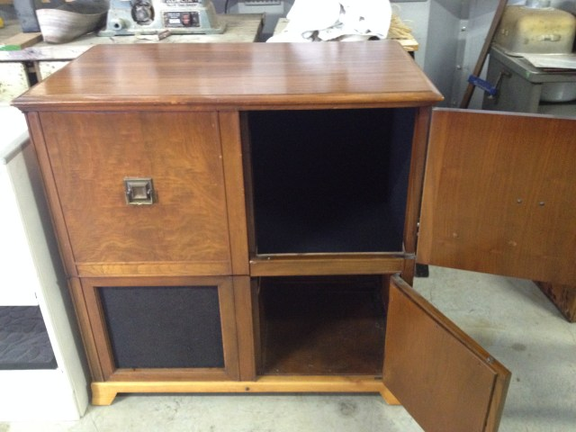 outdated looking solid wood cabinet with four doors in a cube form