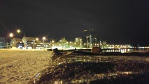 the rocky shore at the bottom of the city of Reykjavik with city lights in the background