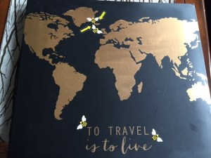 Black 12 x 12 inch cover with gold countries laid out like a map. Stickers of bees surround Iceland and the title, To Travel is to Live.