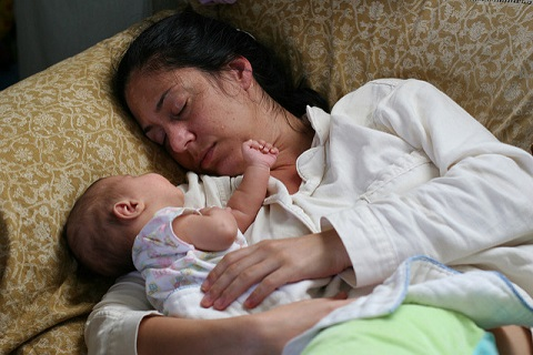 Young Mom and her baby daughter asleep on a couch