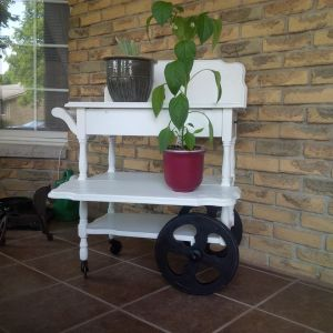 tea trolley now with one leaf attached as a blacksplash, one as a shelf, holding potted plants. Trolley is a fresh white with black wheels
