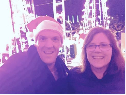 selfie of me and Ken with the backs of the performers behind us, as we stood backstage waiting to go on. I have a tiny santa hat clipped to the side of my head.