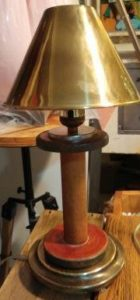 old, wooden sewing machine bobbin about 8 inches tall is now a lamp with a brass shade