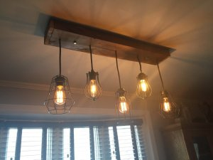 Barnboard base on the ceiling with five pendants suspended at slightly different lengths, each with a metal cage and an Edison bulb