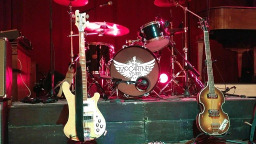 Stage shot of The McCartney Years logo on the bass drum and two guitars on their stands, taken before the show started