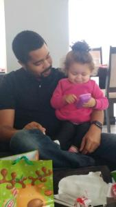 Baby Vienna sits in her Dad's lap, smiling as she presses buttons on a smartphone-sized toy that makes sounds and talks