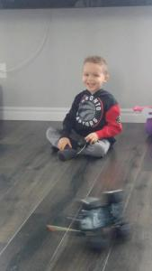 Ryker sitting on the floor with a huge smile on his face while the remote-controlled Jeep passes him in a blur