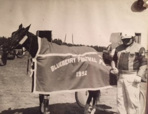 My Dad in his racing suit and helmet standing with his horse, Accumulator, in the winner's circle after winning a race on PEI in 1992