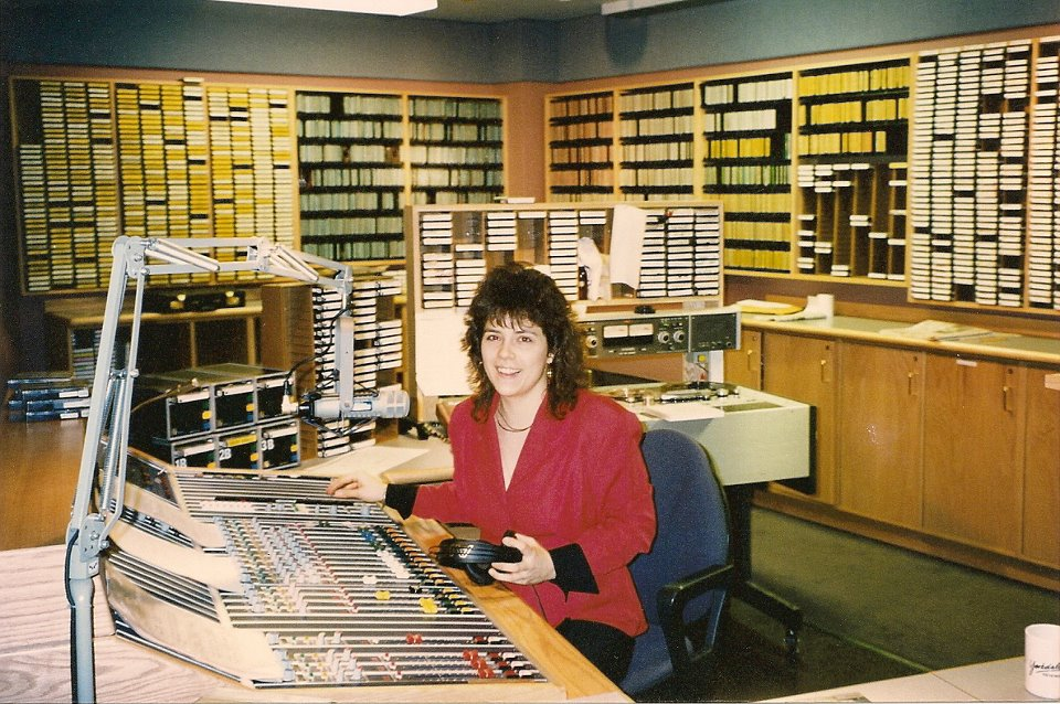 me sitting at the massive control board in the MIX 999 studio at 2 St. Clair West in Toronto. Behind me are racks and racks of carts (cartridges) and CDs. I have permed hair!
