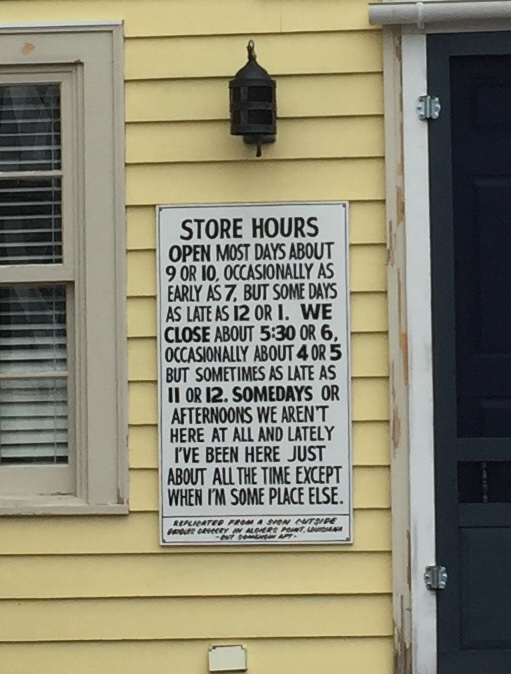 Sign reads: Store hours. Open most days at 9 or 10, occasionally as early as 7 but sometimes as late as 12 or 1. We close most days at 5:30 or 6 but occasionally as early as 4 and sometimes as late as 11 or 12. Somedays or afternoons we're not here at all but lately we've been here just about all the time except when we're somewhere else.