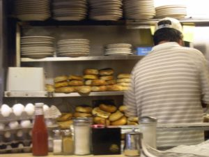 The back of a cook with stacks of plates, eggs and bagels in front of him as he works behind a counter in a diner
