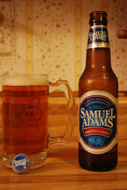 A bottle of Samuel Adams beside a cold glass full of beer