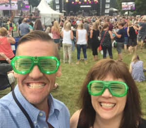 Me and Ken with a crowd and Kim Mitchell on stage in the background. We are wearing green plastic glasses with blinking green lights on them