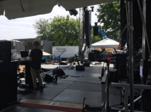 backstage view of mics, gear and a guy doing a soundcheck