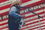 Hank Williams Jr singing on stage in front of a backdrop of an American flag