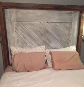 headboard utilizes the bottom of the old door which is now a distressed white. It's framed in oak trim that's been stained medium-dark.