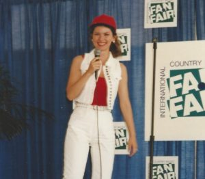 Shania \Twain in white jeans, white sleeveless denim jacket, red top and red hat, looks happy as she walks onto the Fan Fair media stage