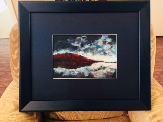 a red mountain reflected in ice-blue water with a dark blue sky and white clouds. Although it's pastel, it's very vivid