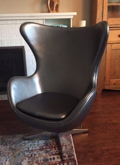 Silver vinyl chair on a metal base. Chair is one big molded piece with arms and a backrest that comes loosely around the side of the head. Its a big char!
