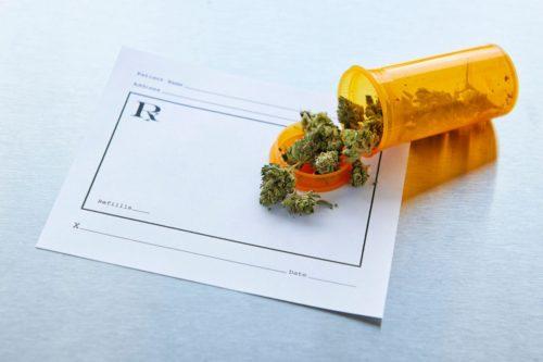Prescription bottle of pot spilled out onto a prescription pad