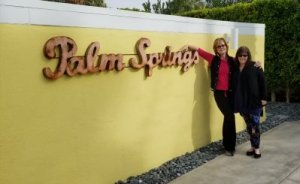 Erin and I arm in arm in front of a yellow wall with metal lettering spelling Palm Springs