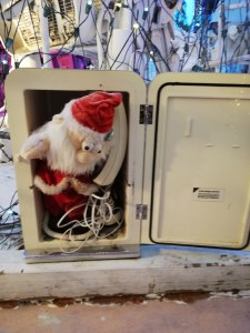 A small santa peeks out of an old telephone box