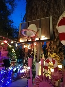 a toilet seat on a backstop as a basketball net with lights and giant candy canes in the background