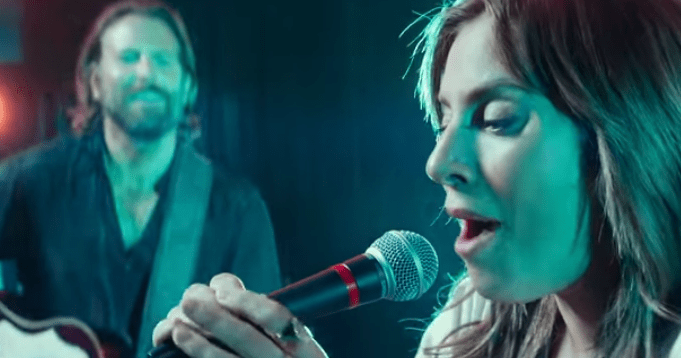 screen shot from A Star is Born. Lady Gaga as Ally performs on stage for the first time while Jack (Bradley cooper) plays guitar and watches in admiration