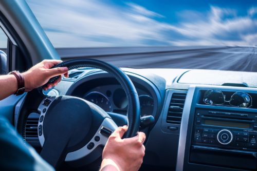 hands on the wheel of a car, and the dashboard, with blue sky and a clear road ahead