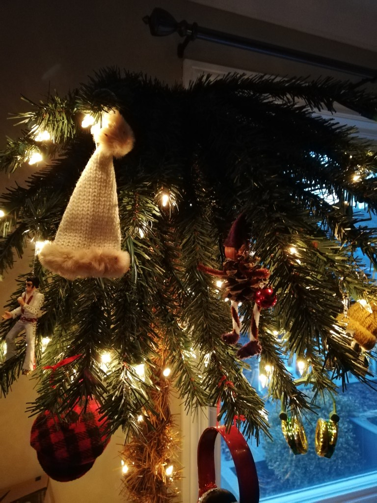 Close-up of the lit palm tree with ornaments including a beige toque, a winter hat, a lumberjack-patterned hat, two sets of headphones and Elvis.