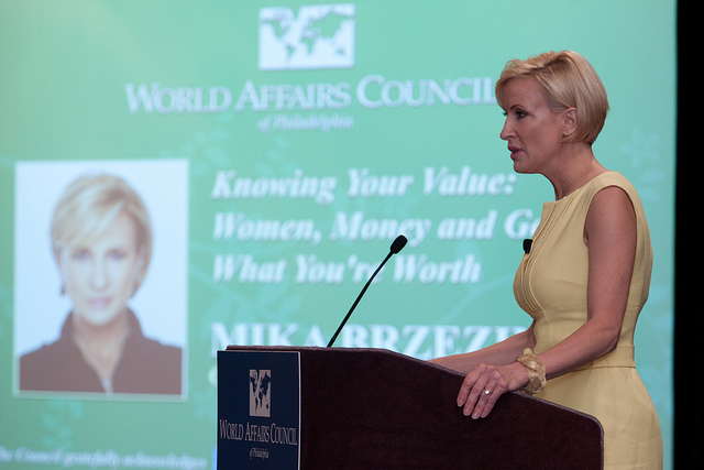 Mika Brzezinski wearing a yellow, sleeveless dress at a podium speaking to the World Affairs Council