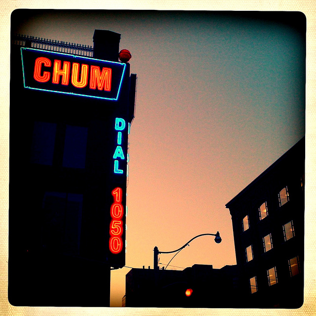 Dusk photo of the iconic CHUM sign with Dial 1050, all lit up in red and blue