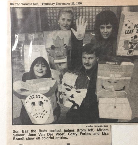 Black and white photo from the Toronto Sun, dated Thursday Nov. 22, 1990. A Sun staffer, our promo director, Gerry and me holding paper bags made into goalie helmets for a contest.