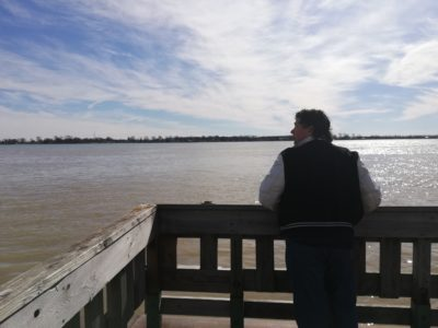 Derek leaning over a railing looking out at the water with a beautiful blue sky ahead of him