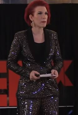 screen capture of sociologist Maja Jovanovic. Tall woman with bright red hair wearing a sequinned silver suit and black top.