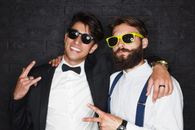 A couple of entitled looking young guys wearing tuxes and sunglasses making rap hand signals to the camera
