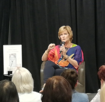 Erin holding a microphone, seated, talking to an audience about her book