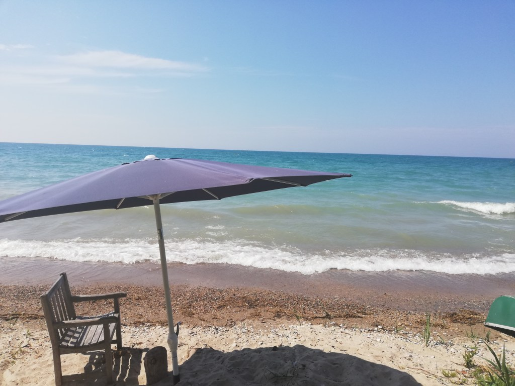 A lawn chair and umbrella about a foot from wet sand as the lake encroaches on beach front.