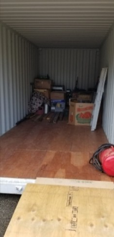 Inside the storage container. It's clean and white with a plywood floor and has about 85% capacity still to be filled. A few boxes are inside.