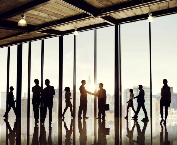 Outlines of eight people chatting or shaking hands against a wall of glass windows.
