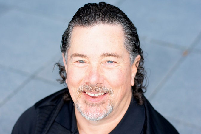 Derek in a photo taken from overhead. He's smiling, wearing a black golf shirt, and it's head and shoulders with a brick background.