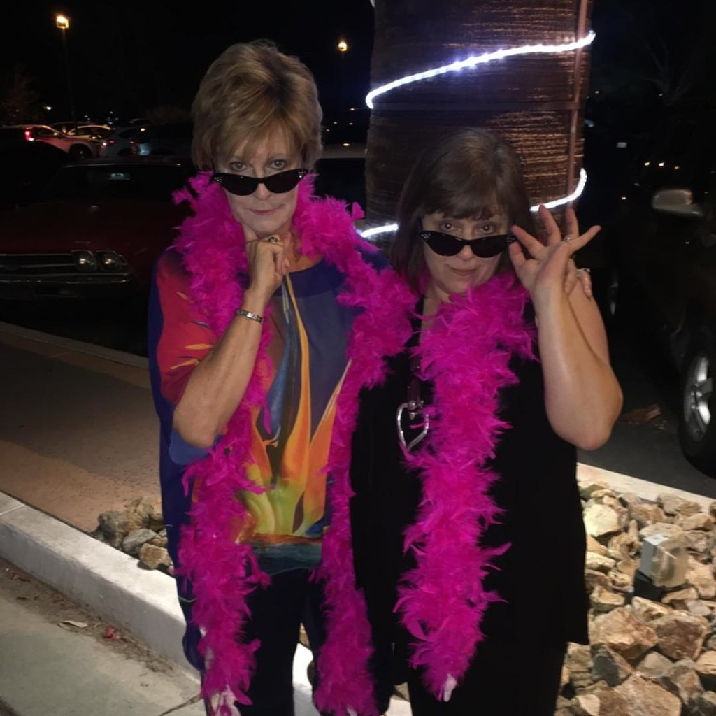 Erin and I wearing pink feather boas and tipping our cats-eye sunglasses down our noses, to the camera.