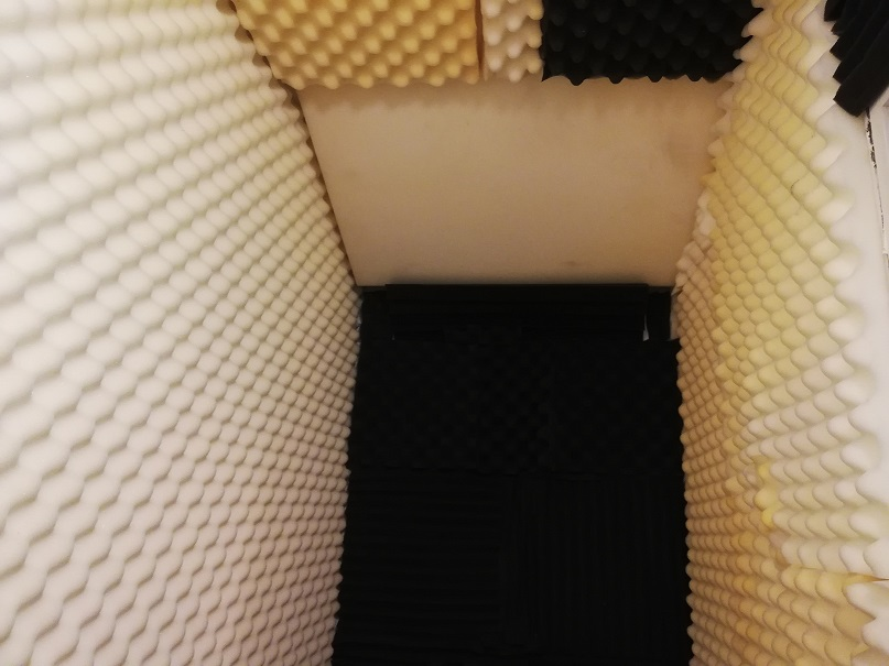 The view inside the deep closet with white acoustic foam on the walls and ceiling and brown foam straight ahead on the end wall.