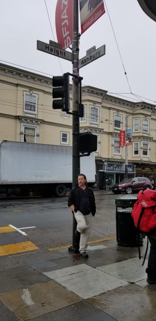 Derek leans against the lamp stand at the corner of Haight and Ashbury.
