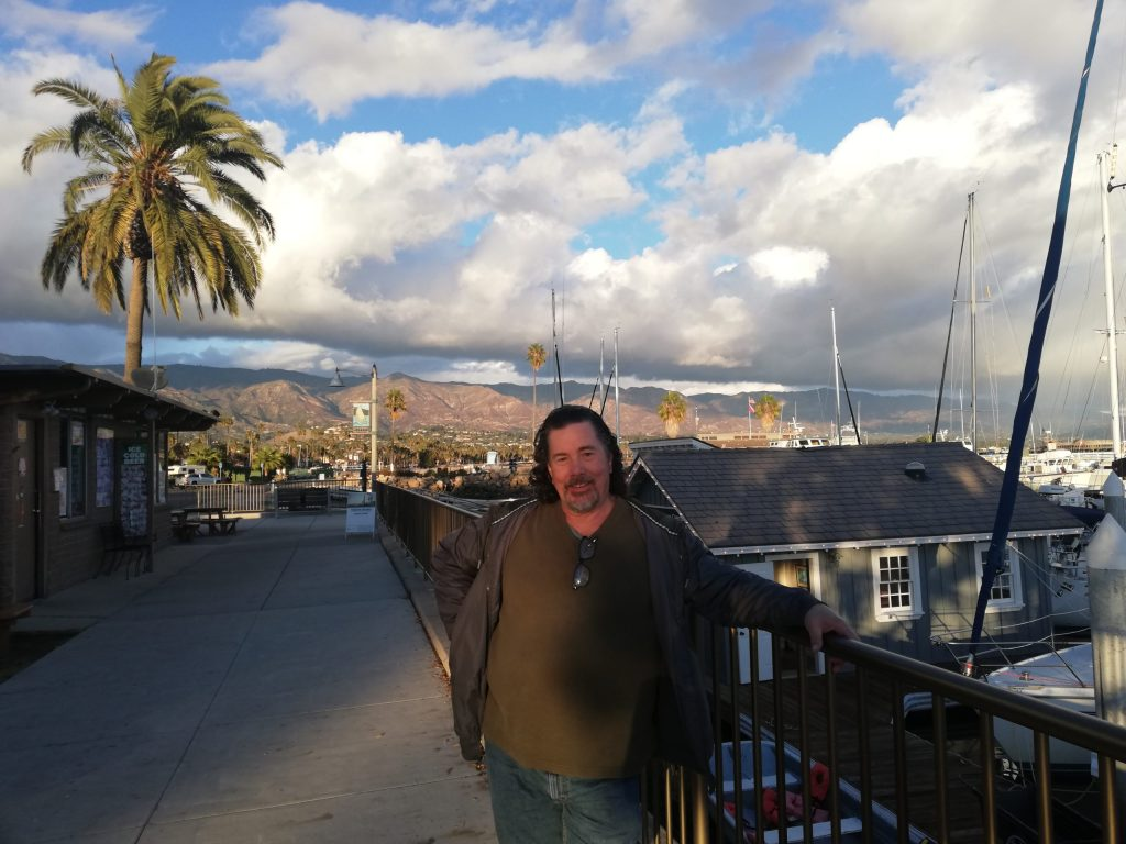 Derek posing in front of the Santa Barbara Marina with blue sky, fluffy white clouds, boat masts and mountains in the background.